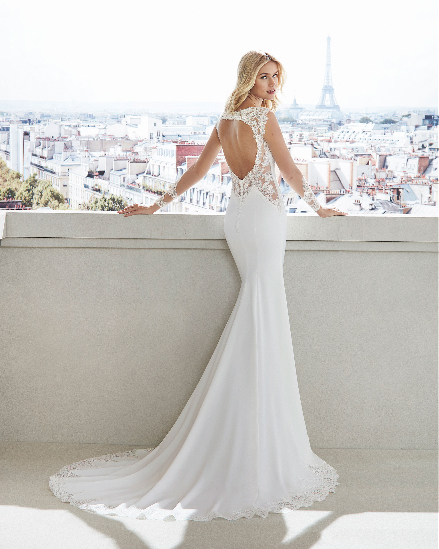 Sheath-style wedding dress in crepe. Lace bodice with bateau neckline, long sleeves, and train with lace insets. Available in natural. 2019  Collection.